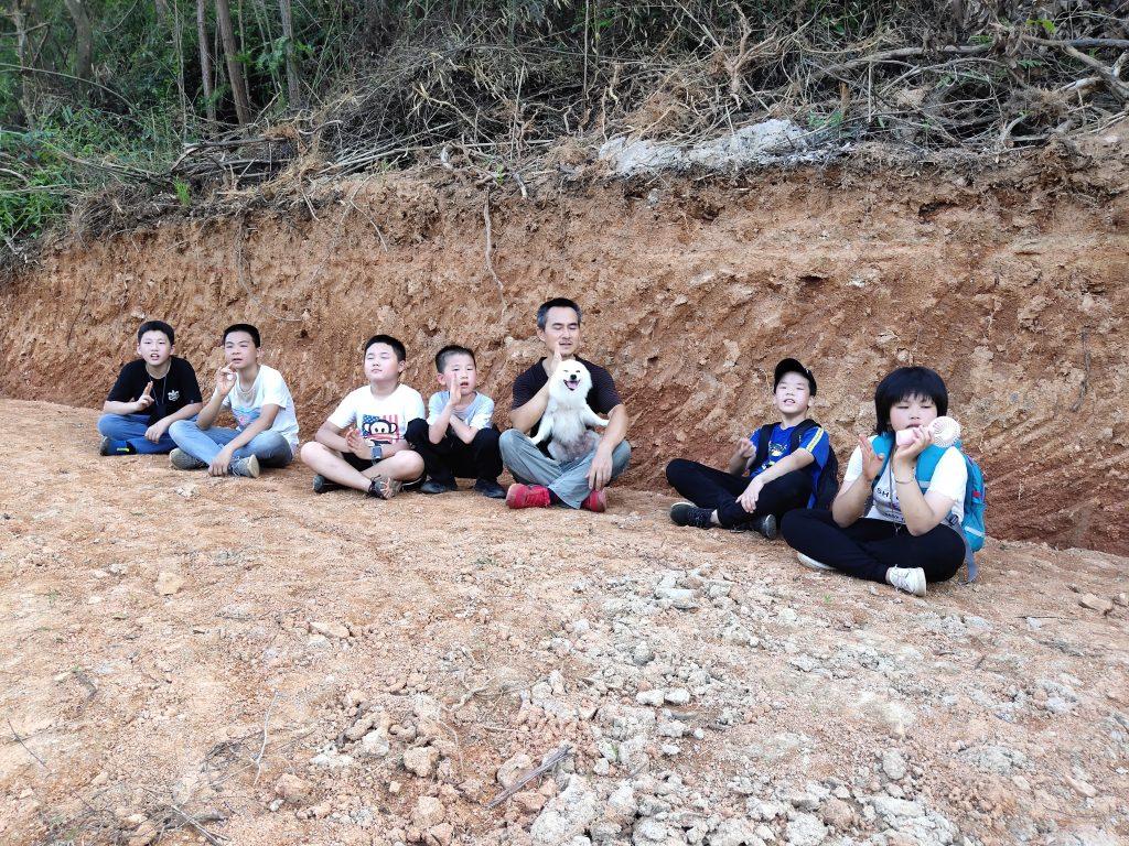 罗老师带着学生在茅坪黄泥地上休息